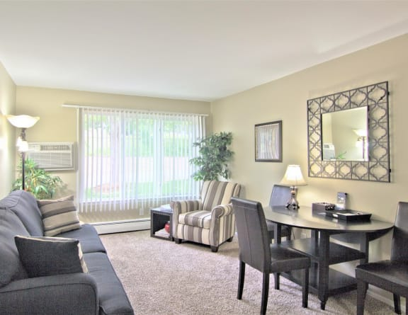Furnished living room with table and chairs and wall decor