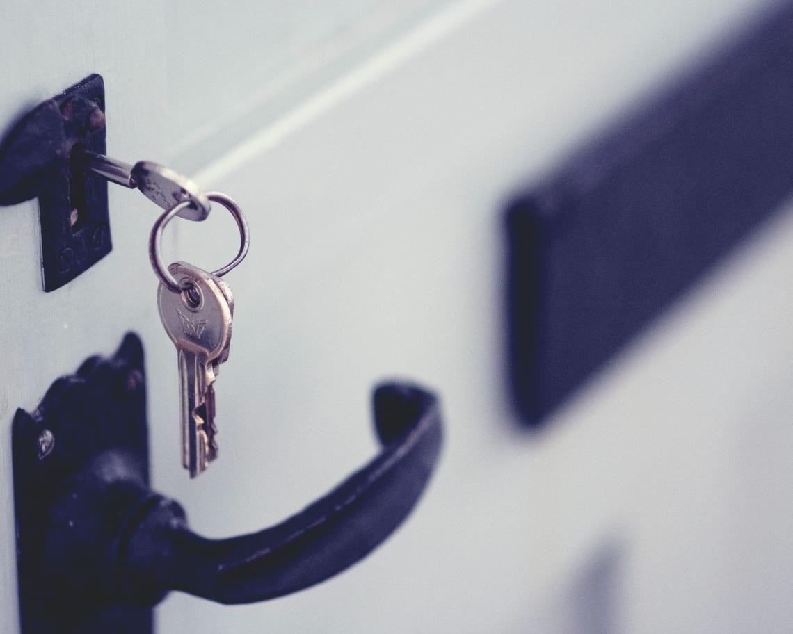Keys hanging in a lock on a white door.