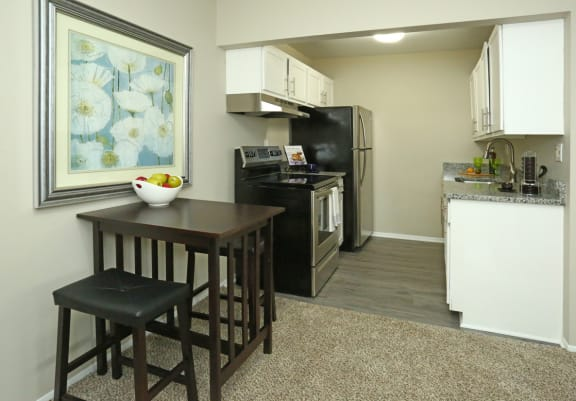 Dining room overlooking kitchen with vinyl flooring and white cabients