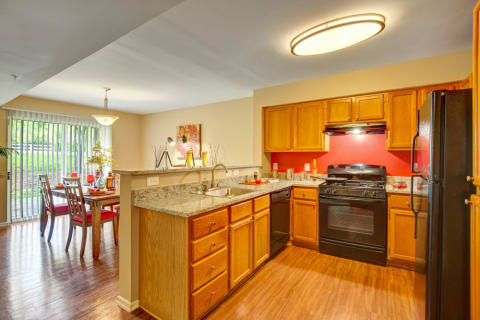 Chef's kitchen with black appliances including dishwasher, disposal, refrigerator, and electric range