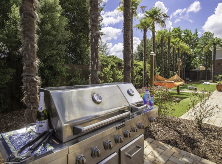 large stainless steel grill at grilling station by pool deck
