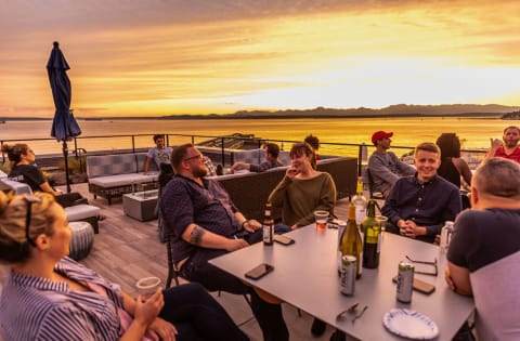 Dinner Party on Rooftop Overlooking Sunset and Seattle Waterfront at 10 Clay Apartments in Seattle, WA