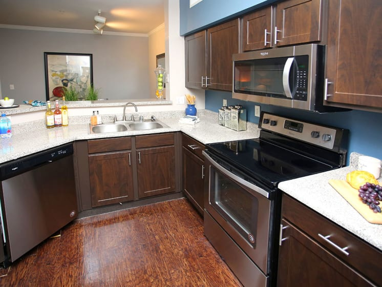 Fully-Equipped Kitchen With Dark Cabinetry and Stainless Steel Appliances at Lost Spurs Ranch Apartments in Roanoke, Texas