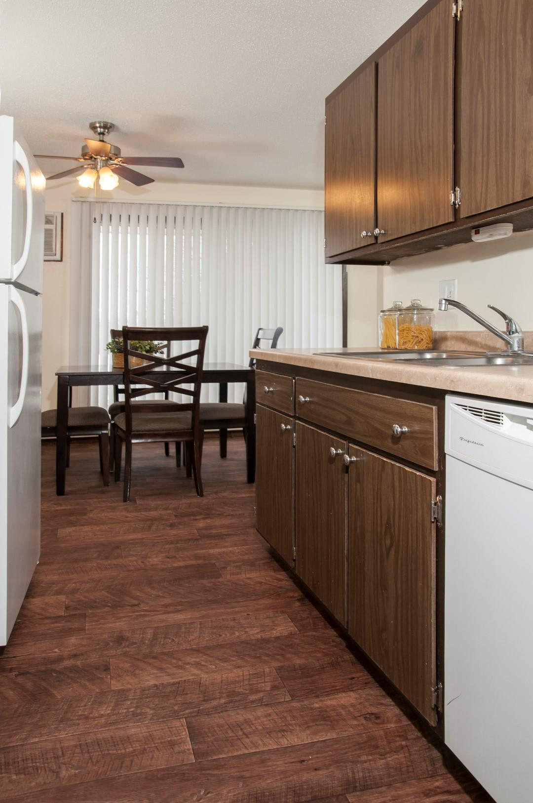 Burnsville Parkway Apartments Kitchen with Dark Wood Cabinetry and White Appliances