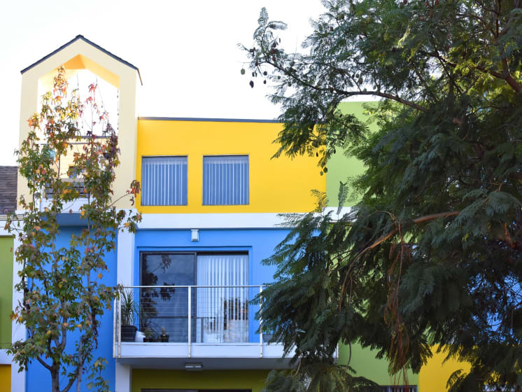 Blue/Yellow Apartment Exterior with View of Private Patio, Trees