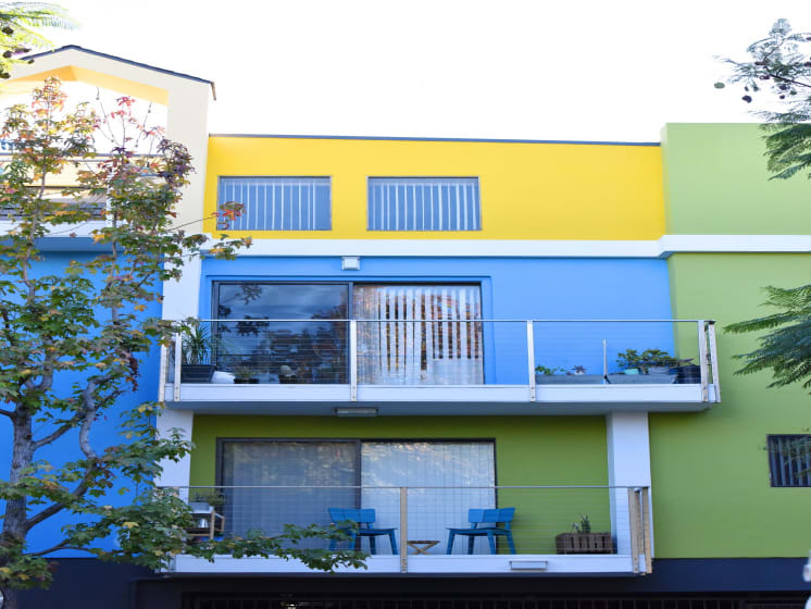 Blue/Yellow/Green  Apartment Exterior with View of Private Patio, Trees