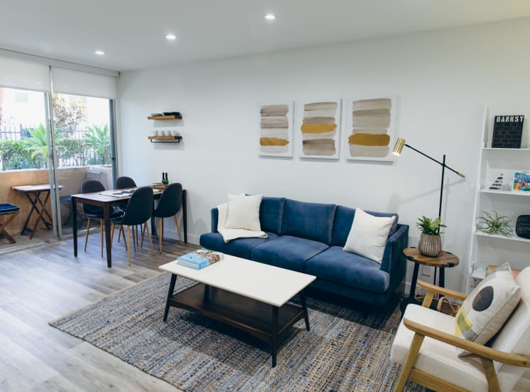 Living room with wood-inspired floors throughout, recessed lighting, dining area and balcony on the left.