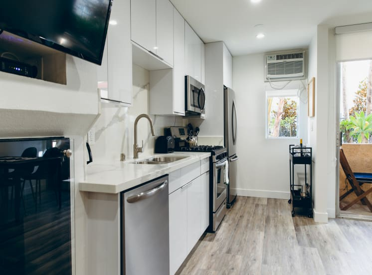 Kitchen with Premium Appliance Packages, stainless steel dishwasher, gas range, micro hood microwave, single kitchen sink, French refrigerator, backsplash and countertops