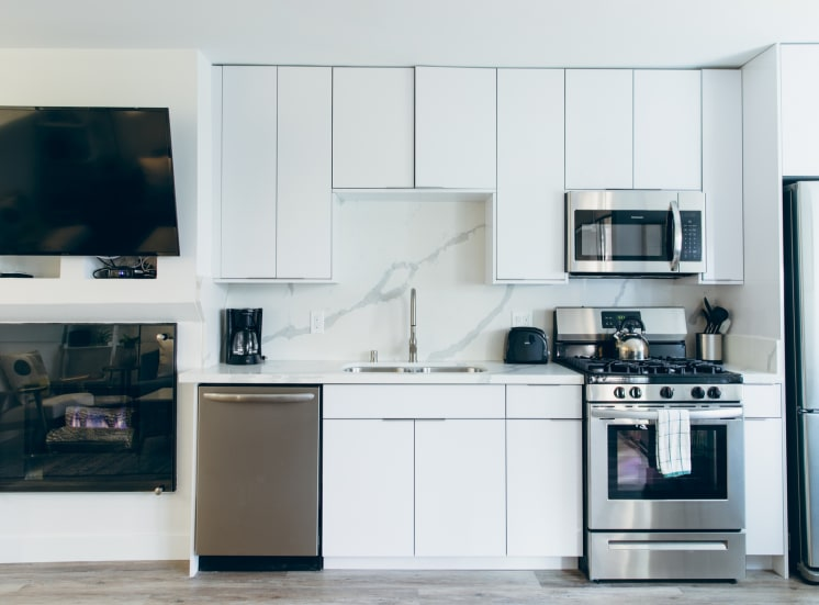Kitchen with stainless steel dishwasher, gas range, micro hood microwave, single kitchen sink, backsplash and countertops, white kitchen cabinets, cozy fireplace on the left