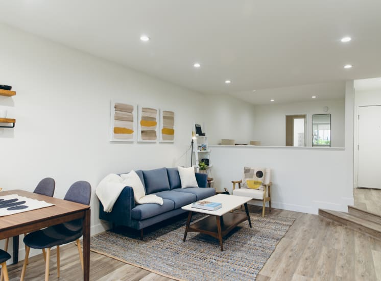 Living room with wood-inspired floors throughout, recessed lighting
