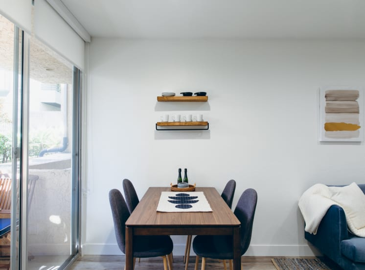 Dining area with wood-inspired floors, balcony on the left. Not all features are available in every apartments