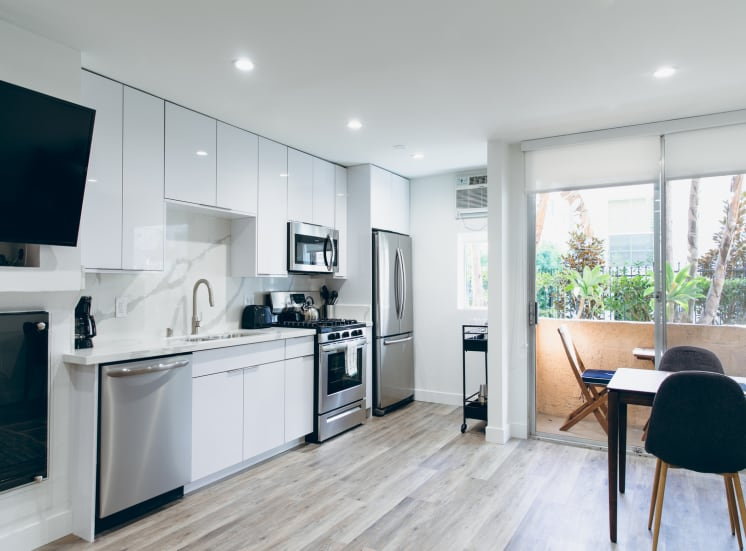 Kitchen with stainless steel appliances, French refrigerator, gas range, micro hood microwave, dishwasher, single kitchen sink, backsplash and countertops, white kitchen cabinets, recessed lighting