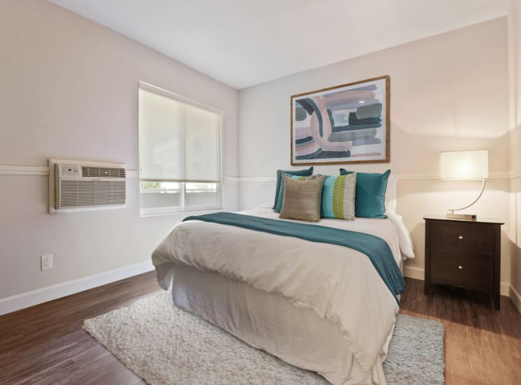 Bedroom with wood-inspired floors, air conditioning, solar shades