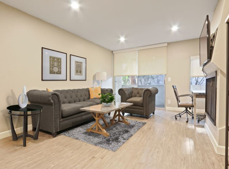 Living room with wood-inspired floors throughout, recessed lighting, fireplace, balcony.
