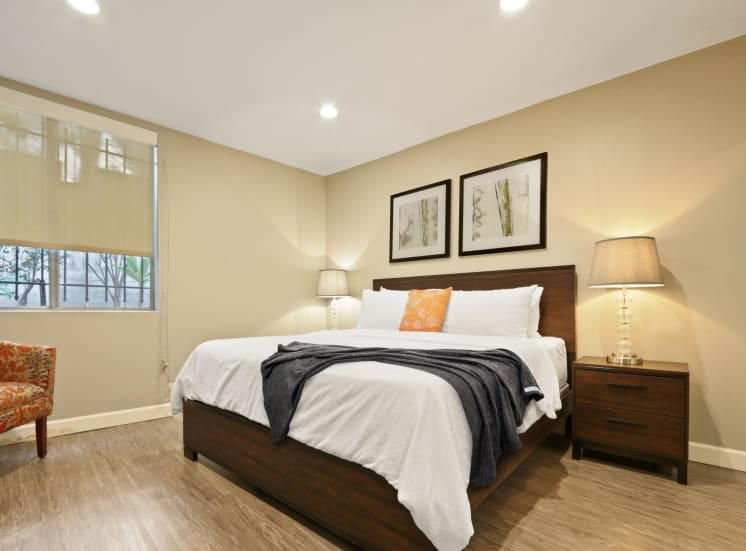 Bedroom with solar shades, recessed lighting, wood inspired floors