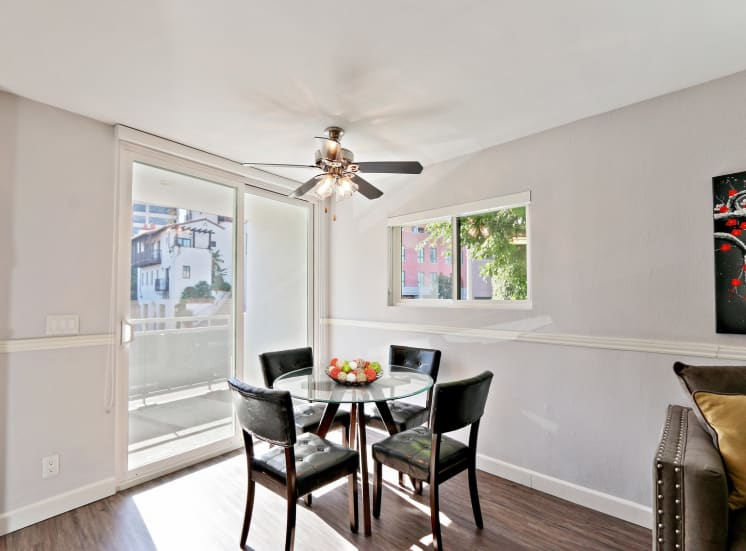 Dining area with ceiling fan, wood-inspired floors, balcony on the left with glass sliding door