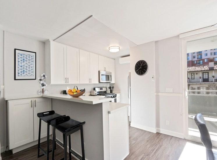 Kitchen with breakfast bar, white quartz countertops. Not all features are available in every apartments