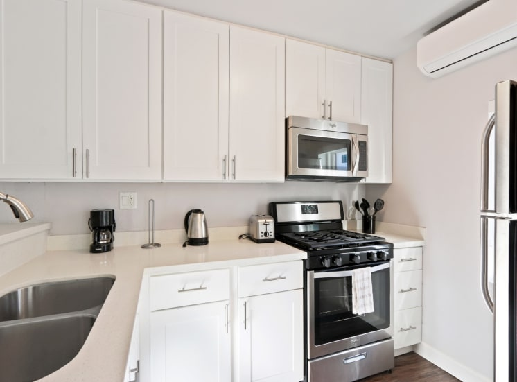 Kitchen with stainless steel double-door refrigerator, gas range, micro hood microwave, double kitchen sink, white quartz countertops, white kitchen cabinets, and wood style floors throughout