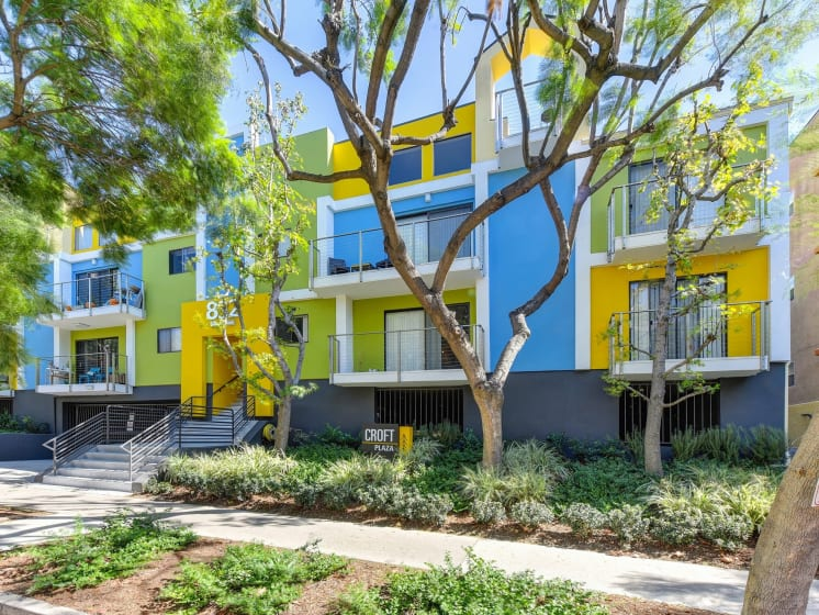 Blue/Yellow/Green  Apartment Exterior with View of Private Patio, Trees, Bushes