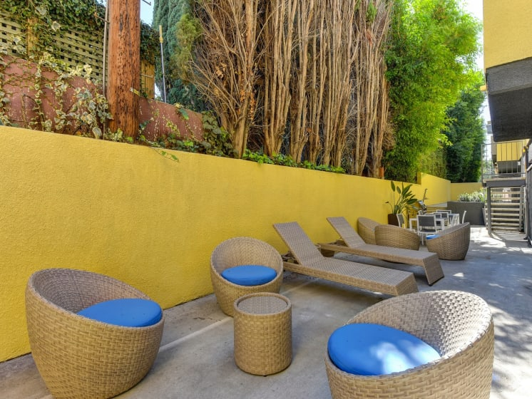 Community Lounge Area with Wicker Seats with Blue Cushions, Wicker Lounge Chairs, Trees, and Yellow Wall