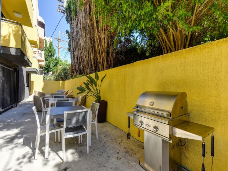 Community BBQ Area with Grill, Picnic Tables, Yellow Wall and Cement Floor