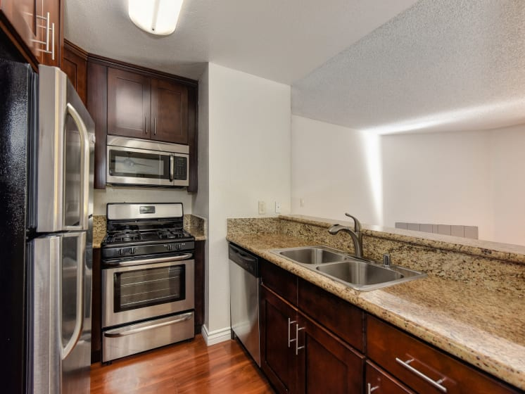 Kitchen with Quartz Granite Countertops, Stainless Steel Refrigerator, Oven, Microwave, And Wood Cabinets