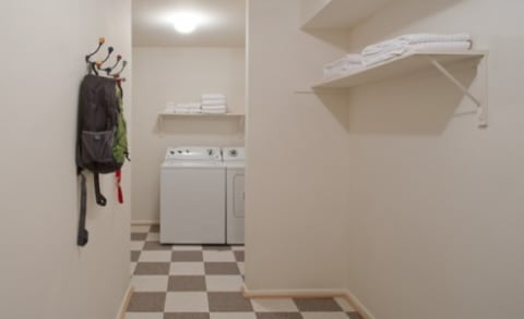 In-Home Laundry Room with a Full-Size Washer & Dryer and Built-in Shelves
