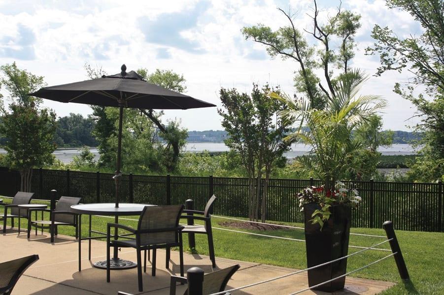 Outdoor patio furniture including tables with an umbrella at Bridgeyard in Alexandria, VA