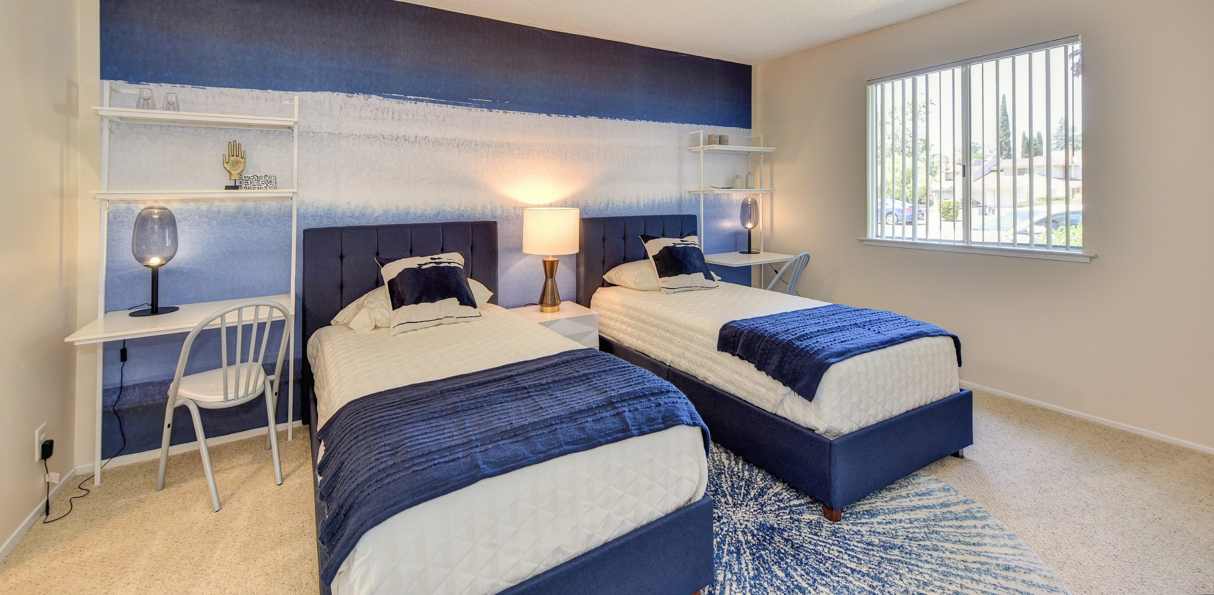 Bedroom with blue and white accent wall and matching bedding.  Small desks on the sides of each of the two beds.