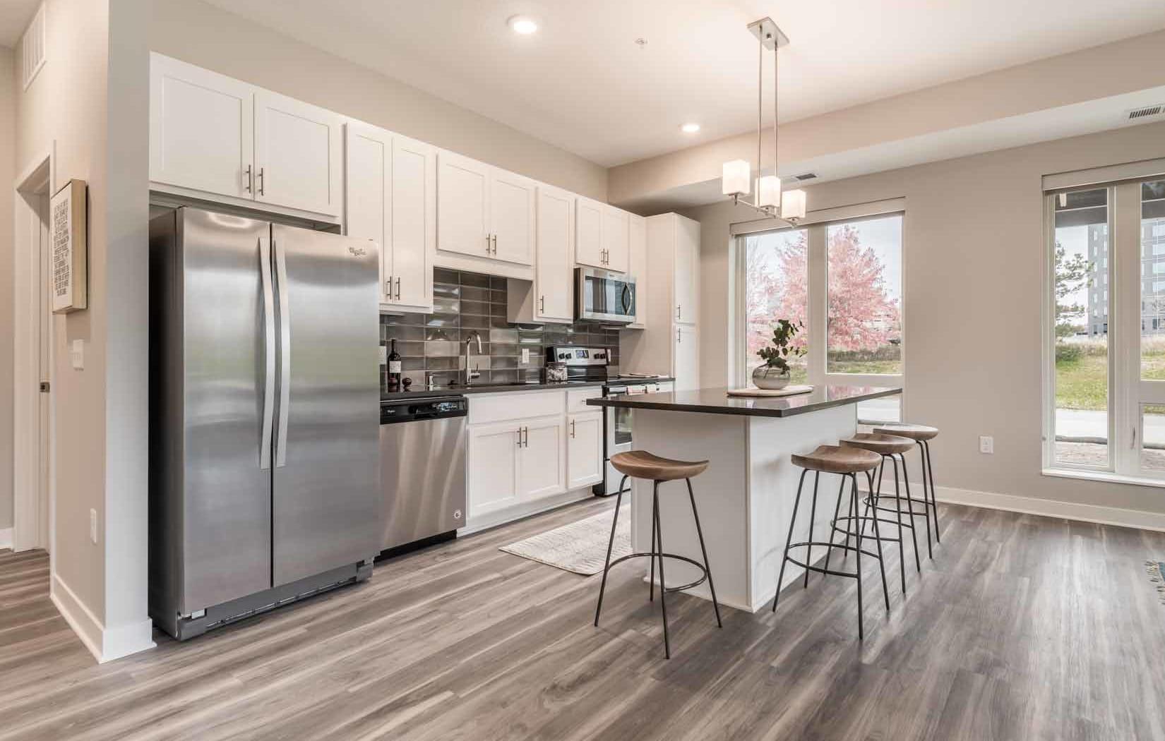 Kitchens feature quartz countertops and designer subway tile