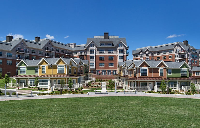 exterior of apartment building and townhouses with grass and benches - Arlington MA luxury apartments