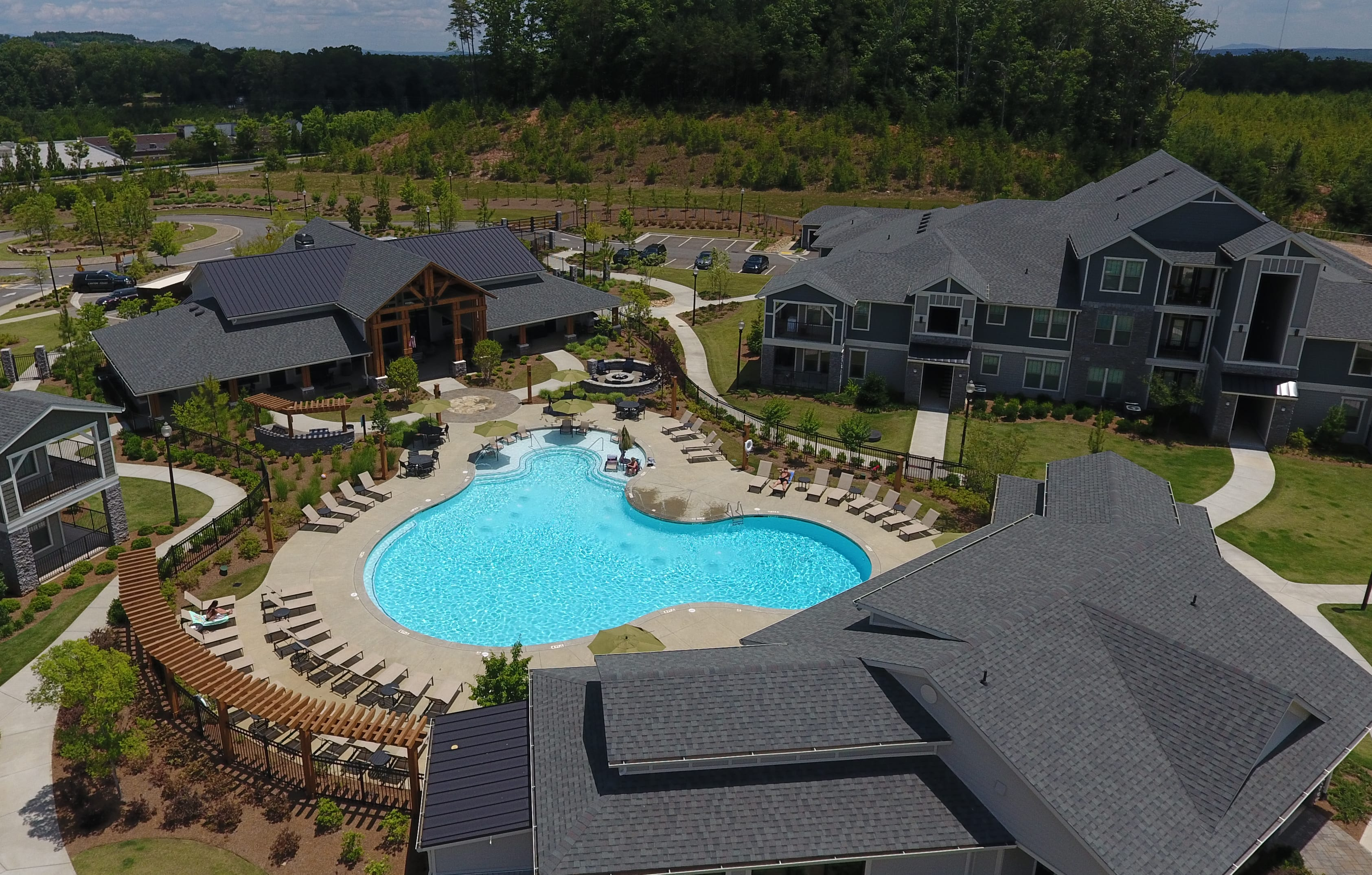 Drone shot view of community showing the resort style pool, leasing office and apartment buildings
