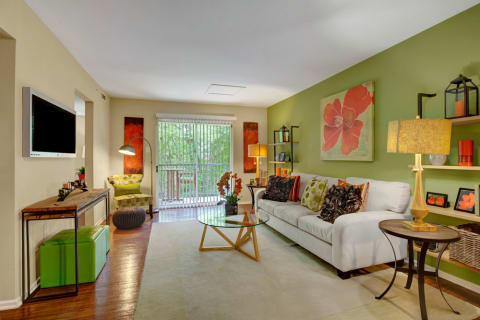 Furnished apartment living room with green walls and wood floors