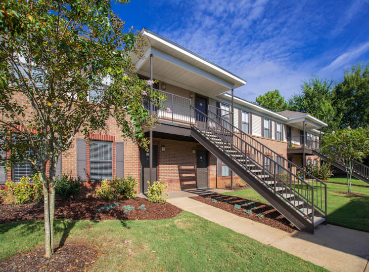 outside of apartment building with large lawn and crepe myrtles