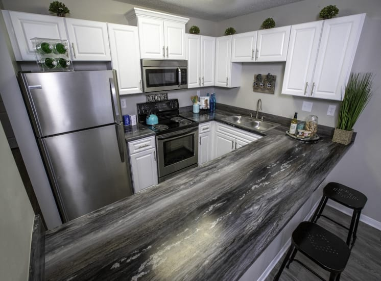 granite style breakfast counter by kitchen with stainless steel appliances and white cabinets
