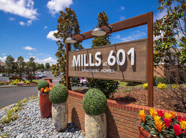 bright blue sky with clouds and The Mills at 601 Entrance sign