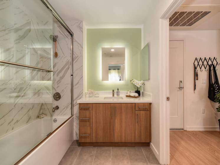 Bathroom with Wood Cabinets, Bathtub, Mirror with Built in Light