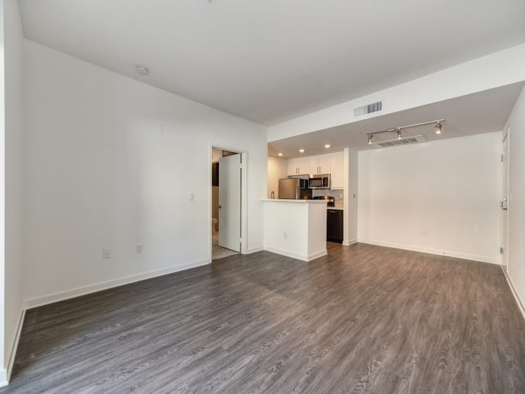 Vacant Living Room with  Hardwood Inspired Floors, View of Kitchen and Ceiling Lights