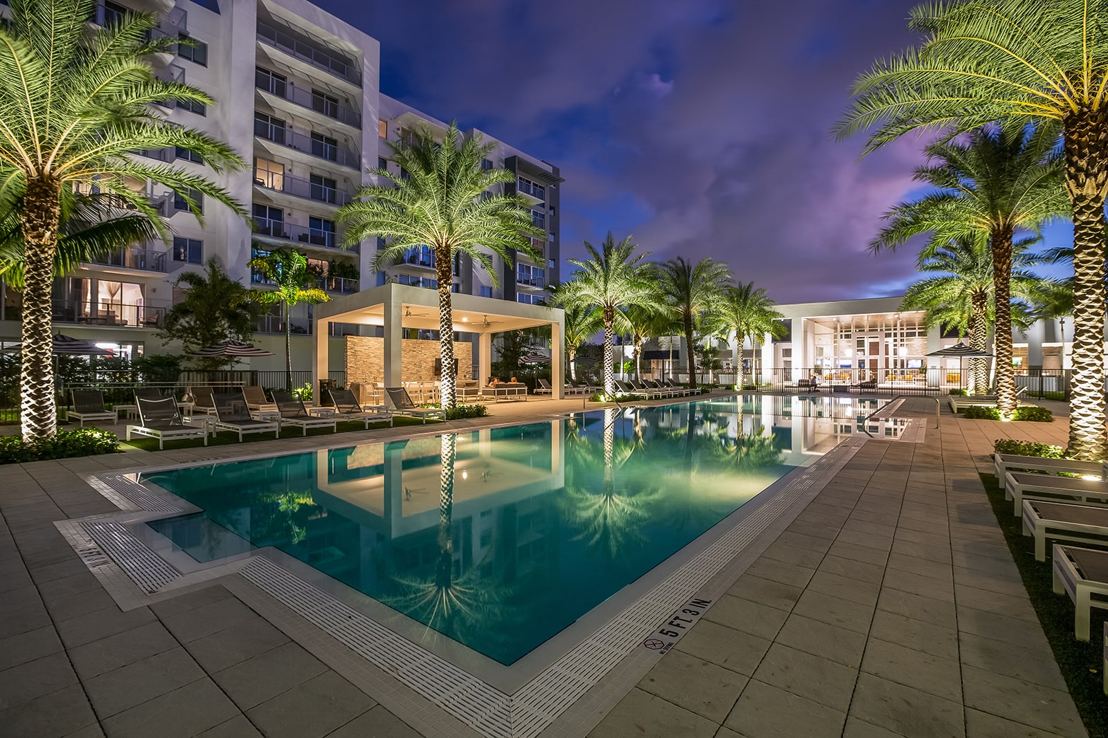 Pool and deck at night at Allure by Windsor, FL, 33487