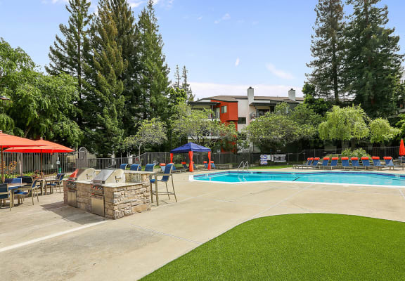 Outdoor grills, pool and apartments in the background