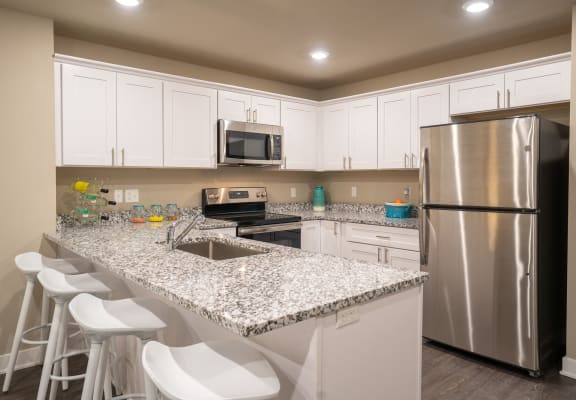 Kitchen with granite counters, stainless appliances, and white cabinets