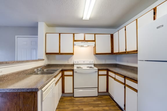 Kitchen featured with white stove, dishwasher and fridge, White cabinets with brown wood trimming and brown/ gray speckled counter tops, brown wood style flooring