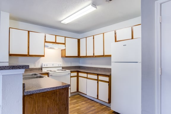 Kitchen featured with white stove and fridge, White cabinets with brown wood trimming and brown/ gray speckled counter tops, brown wood style flooring