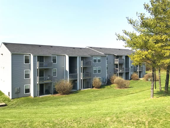 Exterior of an Apartment Building at The Finn Overlooking Green Grass and Trees