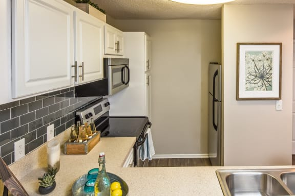 Kitchen with White Cabinetry and Built-In Pantry and Stainless Steel Appliances