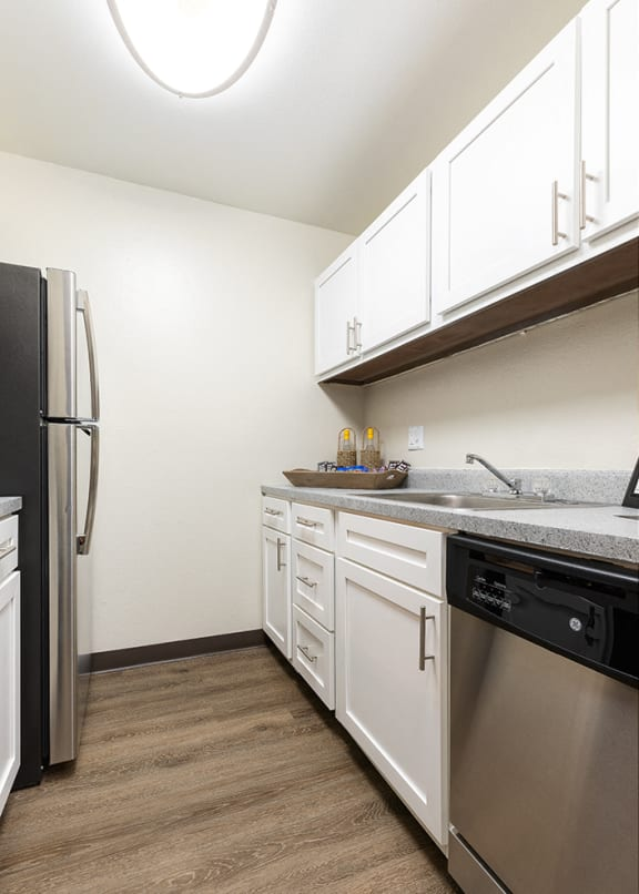 Galley Kitchen with White Cabinetry and Stainless Steel Appliances