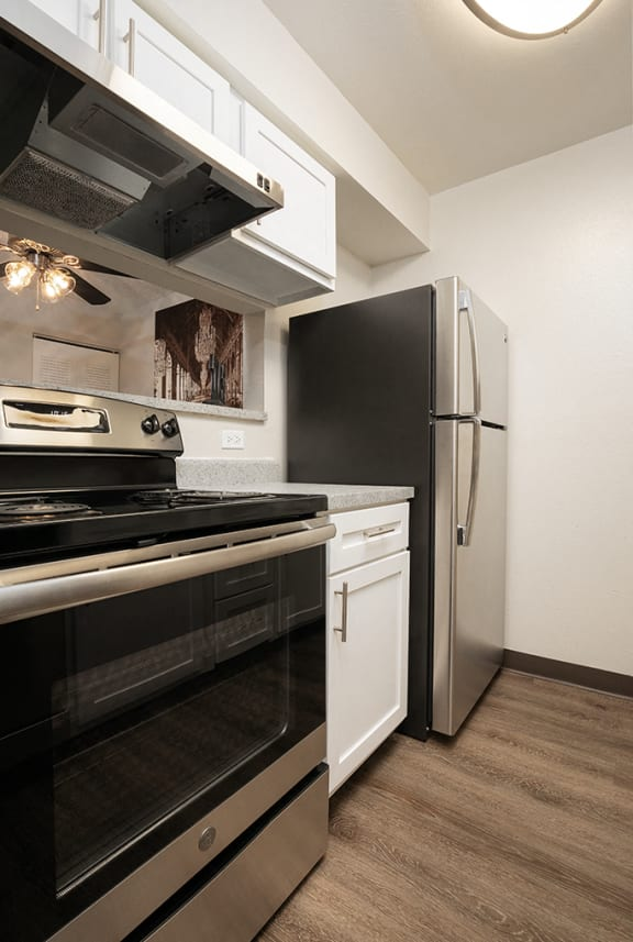 Kitchen with Peek Through Window, White Cabinets and Stainless Steel Appliances