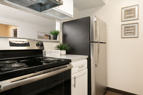 Fully Equipped Kitchen with Stainless Steel Appliances and White Cabinetry