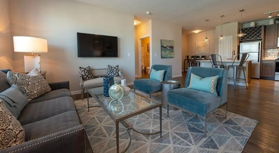 Model living room furnished with a couch and 2 chairs positioned across from it with a coffee table in the middle, looking towards the kitchen and dining area at The Station at Poplar Tent in Concord, NC