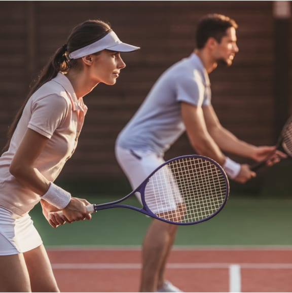 a young man and a young woman playing tennis